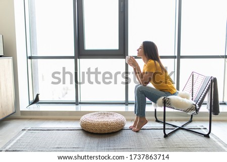 Young woman sitting on modern chair in front of window relaxing in her living room and drinking coffee or tea