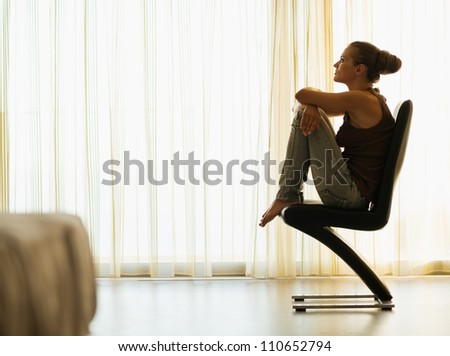 Young woman sitting on modern chair near window