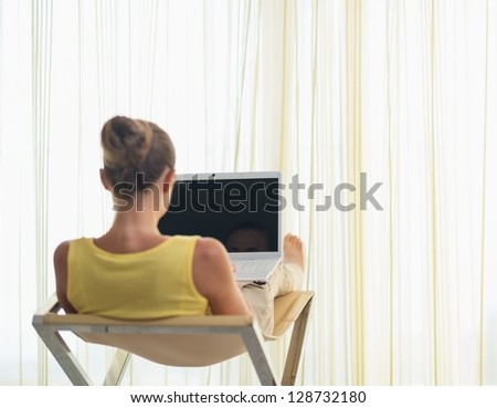 Young woman sitting on modern chair with laptop. rear view