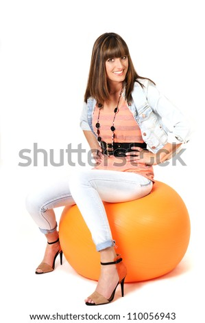 Young woman sitting on orange pilates ball.