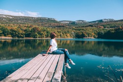 Young woman sitting on peer and enjoying lake view in autumn. Good sunny day for resting outdoors and travel.