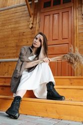 Young woman sitting on porch stairs of a wooden house. She's wearing white jacket over white dress and black heavy boots. Lifting hair with hand, looking at camera.