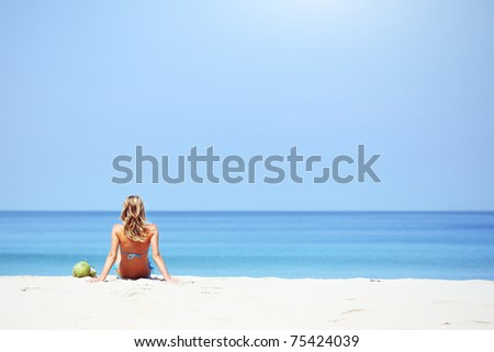 Young woman sitting on sand and looking to a sea