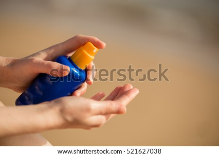 Young woman sitting on sand seashore, holding bottle of sunscreen lotion before applying on tropical beach holiday, close up of hands. Skincare concept #521627038