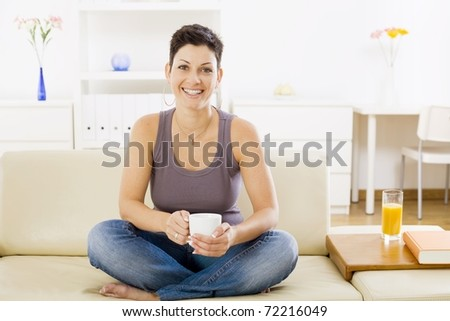 Young woman sitting on sofa at home, drinking coffee.?