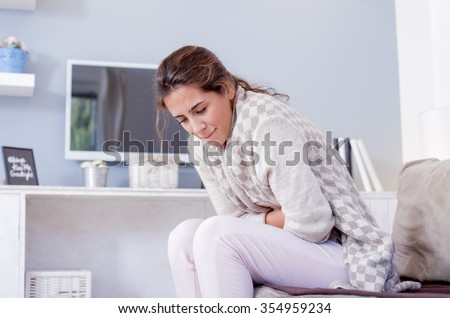 Young woman sitting on the bed with hard stomach pain.\ Shallow depth of field.