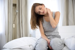 Young woman sitting on the bed with pain in neck