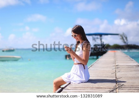 Young woman sitting on the bridge and talking on her phone