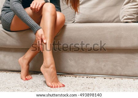 Young woman sitting on the couch suffering from severe pain in the leg #493898140