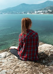 Young woman sitting on the edge and observing beautiful nature landscape with calm sea and island at background