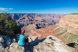 Young woman sitting on the edge of Grand Canyon enjoying the view. Grand Canyon hiker woman resting. Hiking caucasian girl relaxing on  South rim of Grand Canyon, Arizona