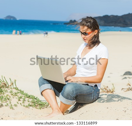 Young woman sitting on the exotic tropical beach with laptop computer