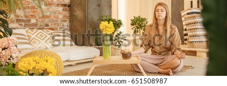 Young woman sitting on the floor at home and meditating #651508987