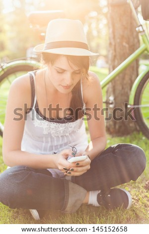 Young woman sitting on the grass and using smart phone.