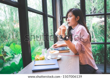 Young woman sitting on the grass drinking coffee and reading a book enjoys outdoor recreation,Young woman working on her tablet in a coffee shop