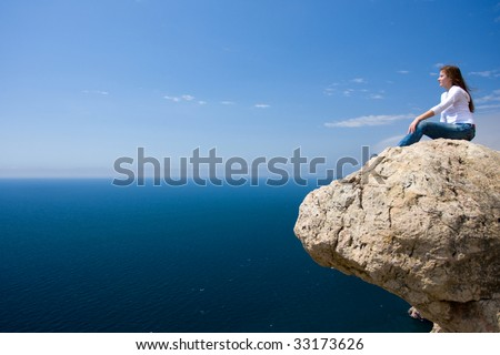 young woman sitting on the rock near the sea