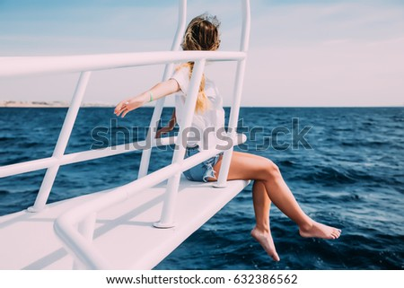 Young woman sitting on the ship deck enjoying the moment on a sunny day. Copy space #632386562