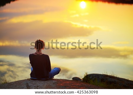 Young woman sitting on the stone enjoying peaceful moment of sunset. In the reflection of the lake water sees clouds and sun. Inner mind open, harmony life up in dusk sky, destiny, god, zen concept