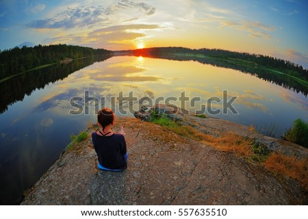 Young woman sitting on the stone enjoying peaceful moment of sunset. In the reflection of the lake water sees clouds and sun. #557635510