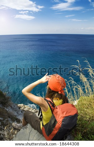 young woman sitting on top of a cliff and looking up to the sky