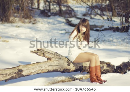 young woman sitting on tree