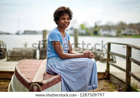 Young woman sitting on upturned boat.