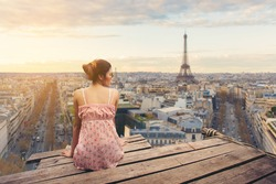 Young woman sitting on wood pier looking Eiffel tower, back view.