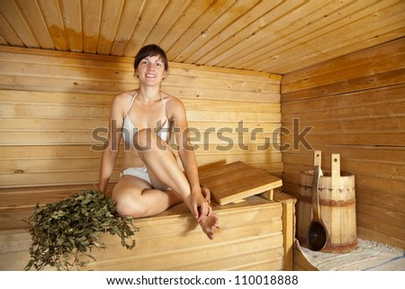 Young woman  sitting on wooden bench  at sauna