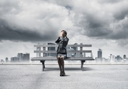 Young woman sitting on wooden bench outdoors. Girl in business suit keeps hands on face for surprise. Hide from problems. Help and successful solutions. Modern cityline panorama with storm sky.