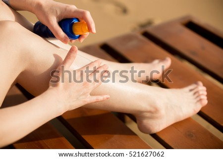 Young woman sitting on wooden sun lounger on sunny southern sand beach, holding bottle of sunscreen lotion, applying sunblock cream on legs, close up. Sunburn and cancer protection concept #521627062