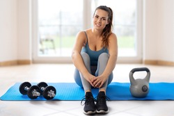Young woman sitting on yoga mat during home workout