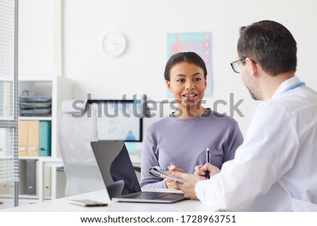 Young woman sitting opposite the doctor and talking to him while sitting at his office stock photo