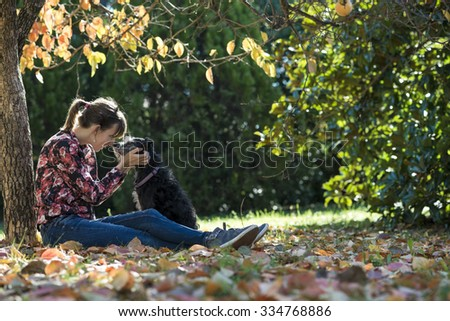 Young woman sitting under a colorful autumn tree lovingly petting her black dog as they join their noses in affection.