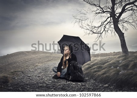 Young woman sitting under an umbrella under cloudy sky