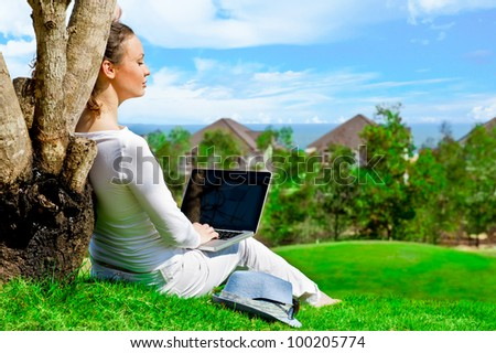 Young woman sitting under tree with laptop and dreaming. Idyllic outdoor scenery