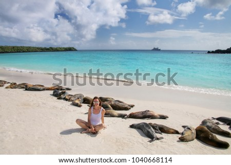 Young woman sitting with a group of Galapagos sea lions at Gardner Bay, Espanola Island, Galapagos National park, Ecuador. These sea lions exclusively breed in the Galapagos.