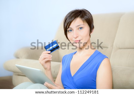 Young woman sitting with digital tablet and holding a credit card.