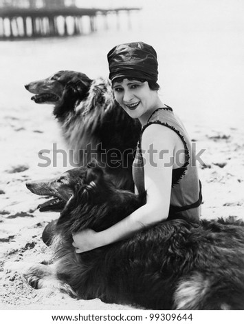 Young woman sitting with her Collies on the beach