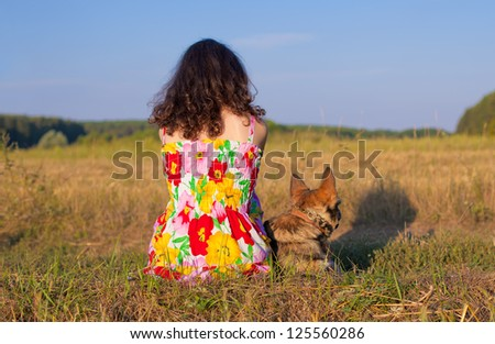 Young woman sitting with her dog  back to camera on the meadow at sunset.