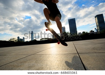 young woman skateboarder skateboarding at city #668601061