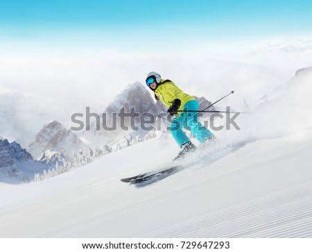Young woman skier running down the slope in Alpine mountains. Winter sport and recreation, lesure outdoor activities.