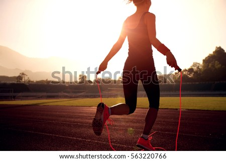 Young woman skipping rope during sunny morning on stadium track #563220766