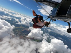Young woman skydiver jumping from the plane performing front loopings. Fearless and confident.