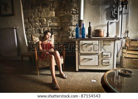 Young woman sleeping in an old kitchen
