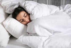 Young woman sleeping in bed covered with white blanket