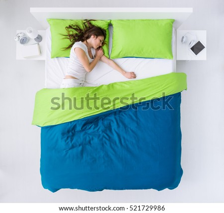 Young woman sleeping in her bedroom, she is resting and dreaming, top view