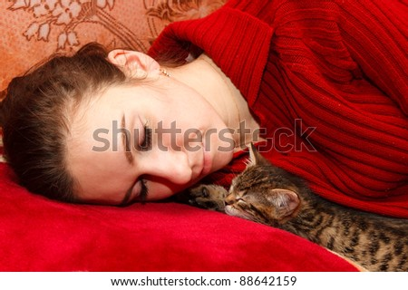 young woman sleeping on bed with kitten