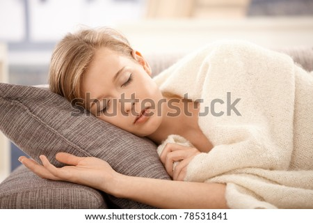 Young woman sleeping on sofa at home, covered with blanket.?