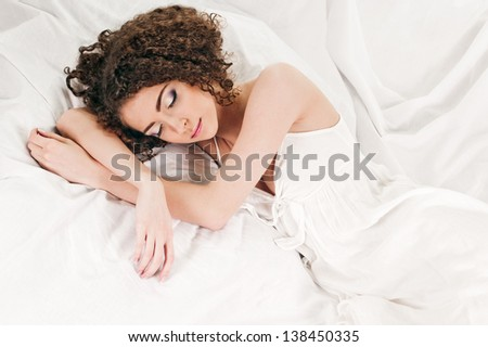 young woman sleeps on the white bed