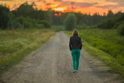 Young woman slowly walking on dirt road in dark summer evening. Orange sunset light in sky. Spending time alone in nature. Peaceful atmosphere. Back view.